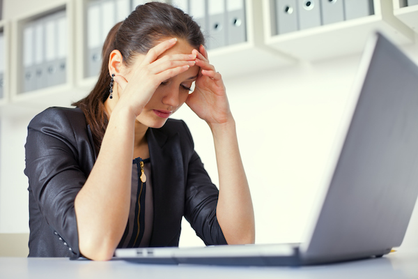 Tired young business woman with laptop